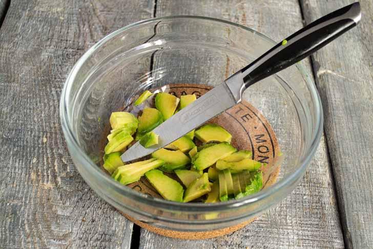 Режем авокадо тонкими ломтиками и кладём в салатницу