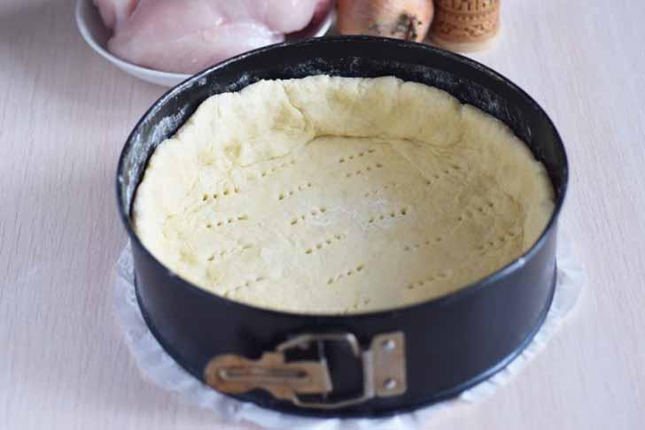 Переносим на подготовленную форму пласт из теста и формируем каркас для пирога, накалываем его вилкой