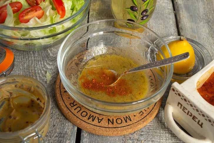 Наливаем в миску оливковое масло, насыпаем сладкую паприку или красный перец. Смешиваем заправку ложкой